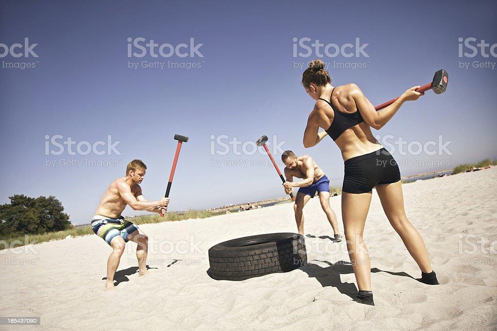 Athletes doing gym workout on beach royalty-free stock photo