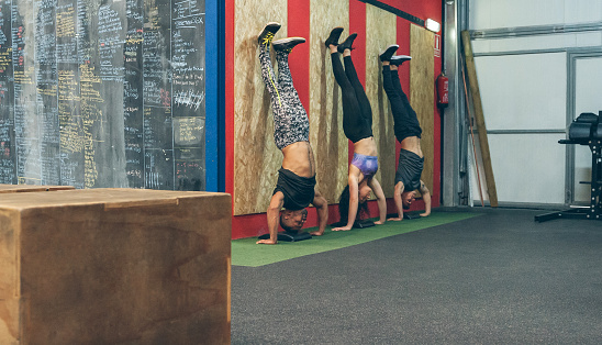 istock Athletes doing headstands in the gym 1181147284