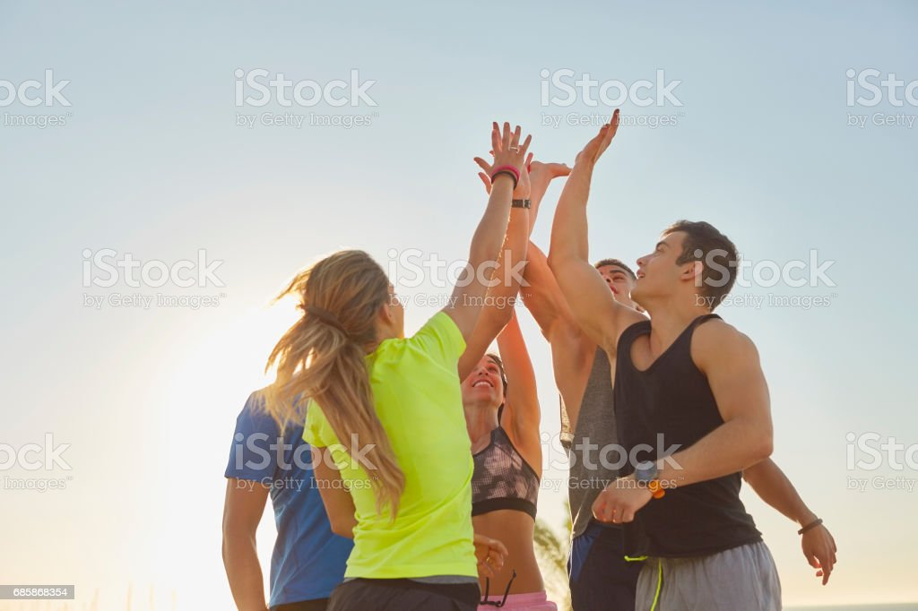 Athletes doing high-five on promenade stock photo