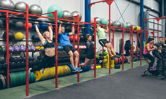 istock Athletes doing pull ups and air bike in the gym 1176987564