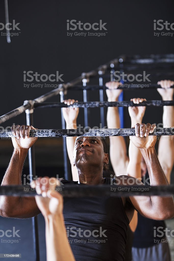Athletes doing pull-ups in gym stock photo