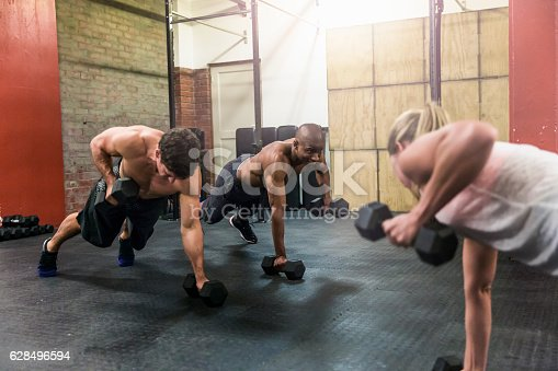 1069872470 istock photo Athletes exercising with dumbbell at brightly lit gym 628496594
