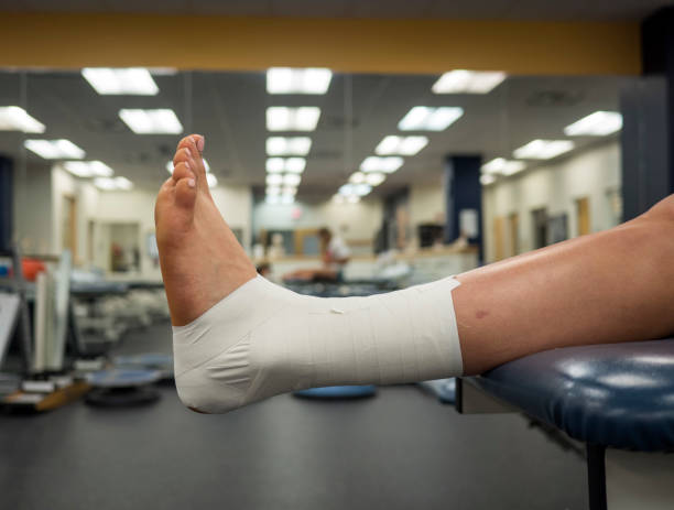 Athlete's foot with an ankle tape job for support hanging off a table in a medical clinic stock photo