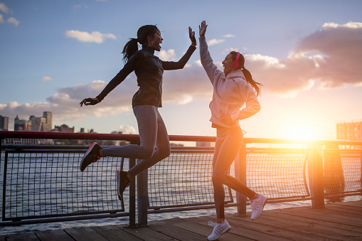 istock Athletes giving high-five by river during sunset 671472134