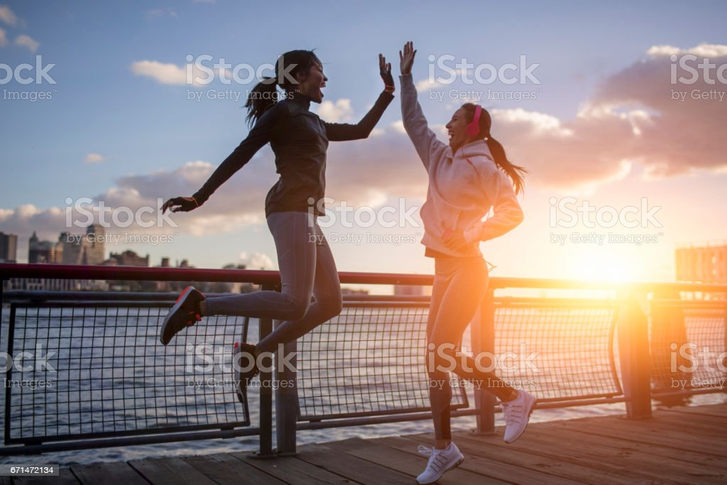 Athletes giving high-five by river during sunset - foto stock