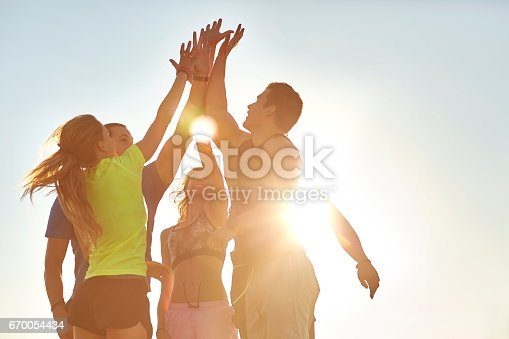 Low angle view of athletes high fiving after successful workout. Male and female friends are in sportswear. They are against clear sky on sunny day.