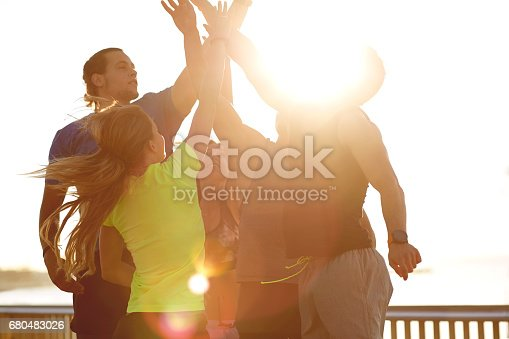 670054434istockphoto Athletes high fiving after successful workout 680483026