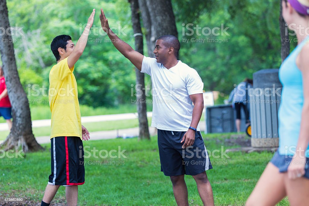 Athletes high fiving after workout in park on sunny day stock photo