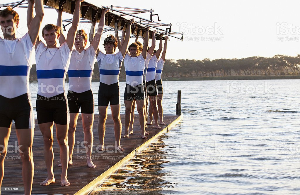 Athletes holding a crew canoe over heads royalty-free stock photo