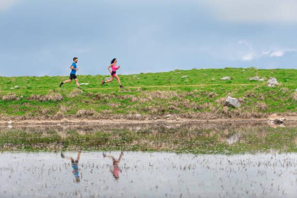 Athleten im Training in den Bergen spiegeln sich im See wider, wenn sie laufen – Foto