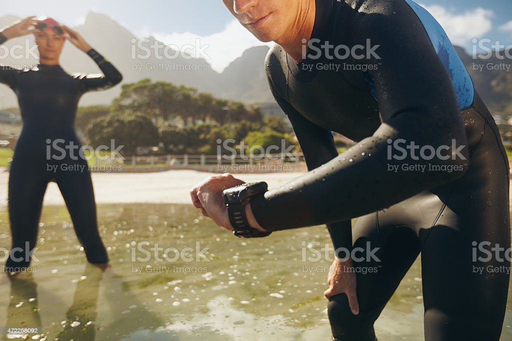 Athletes in wet suits preparing for triathlon competition stock photo