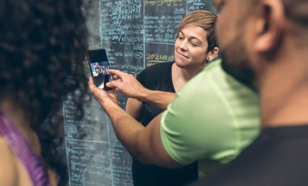 atleten kijken naar de mobiele van een gym mate - call center stockfoto's en -beelden