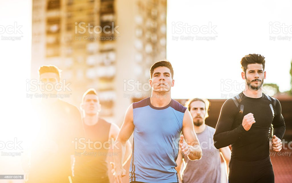 Young men having a sports race on a stadium at sunset.