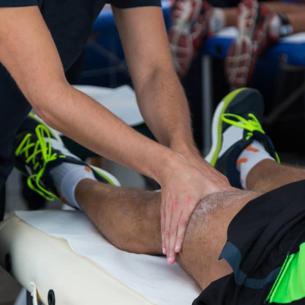 músculos masaje profesional tratamiento de atleta después del entrenamiento deportivo, fitness y wellness - masaje deportivo fotografías e imágenes de stock