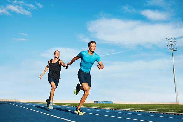 sportler an das baton relay in einem track - staffelstab stock-fotos und bilder