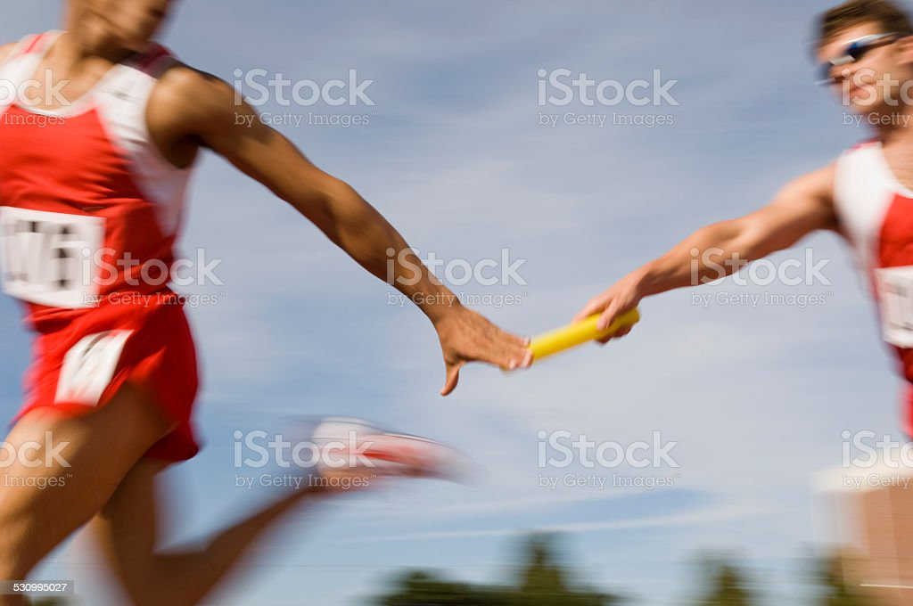 Athletes passing relay baton stock photo