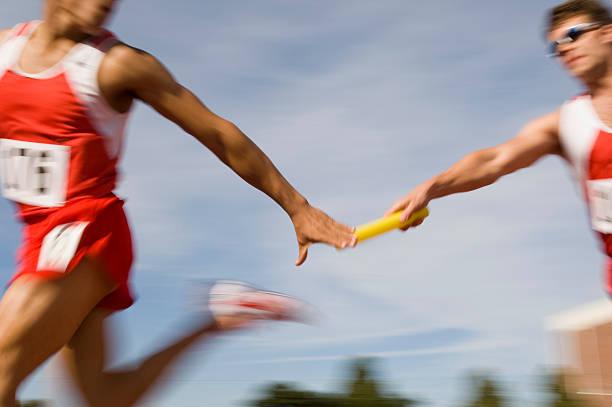 athleten übergeben staffelstab - staffelstab stock-fotos und bilder