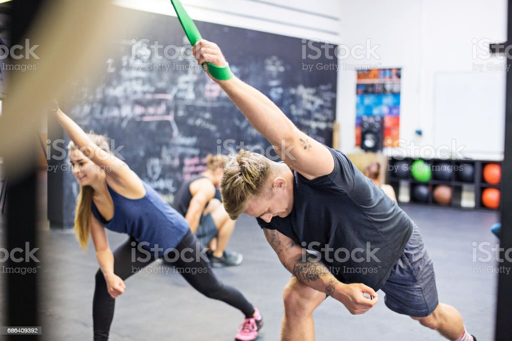 Athletes pulling resistance bands in gym stock photo