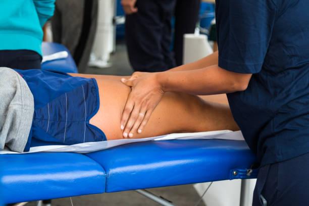 cuádriceps de atleta muscular profesional tratamiento masaje después de entrenamiento deportivo, fitness y bienestar - masaje deportivo fotografías e imágenes de stock