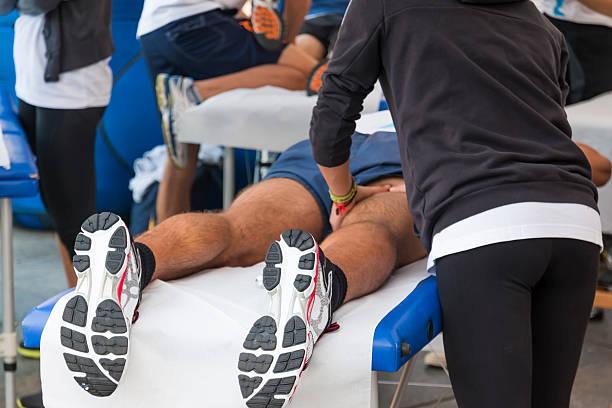 atletas masajes de relajación antes de eventos de deportes - masaje deportivo fotografías e imágenes de stock