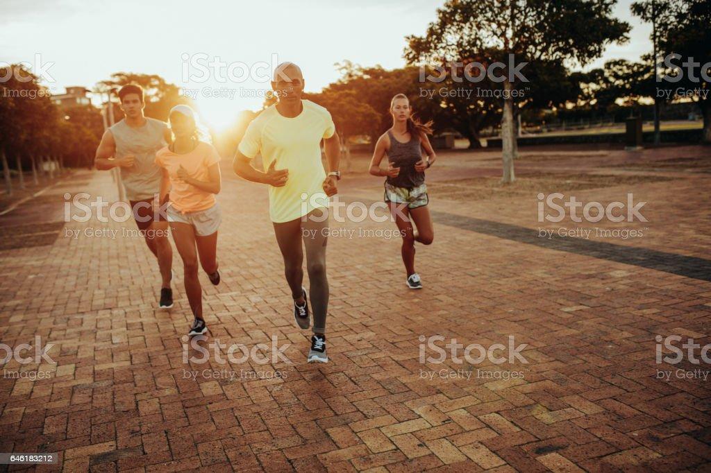 Athletes running at the city park stock photo