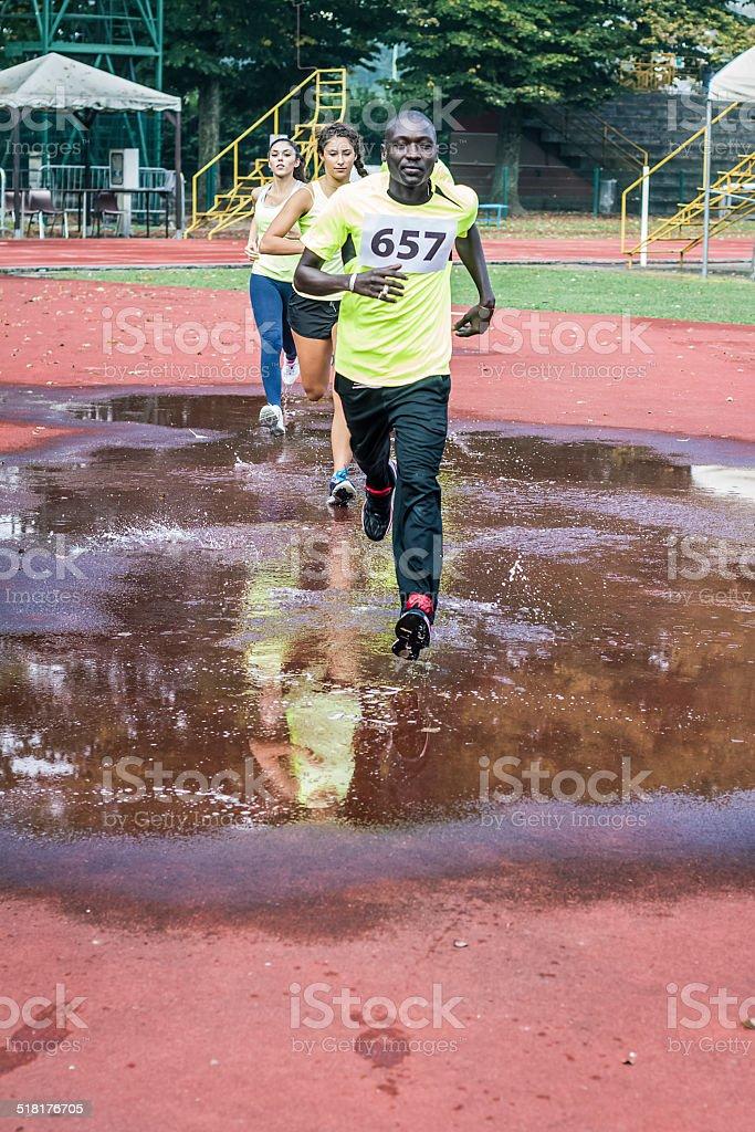 Athletes running on puddle stock photo