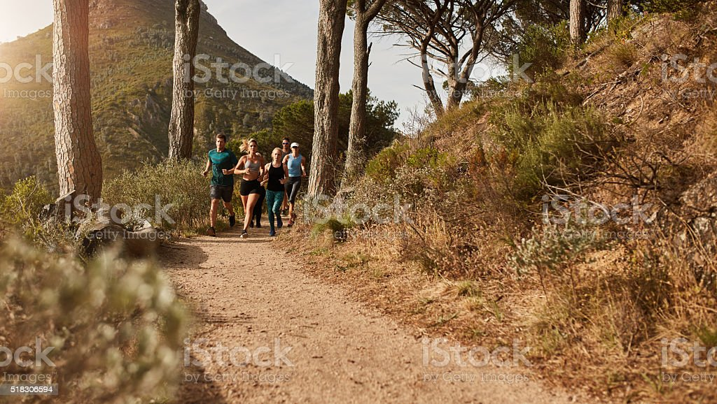 Athletes running together through trails on the hillside stock photo