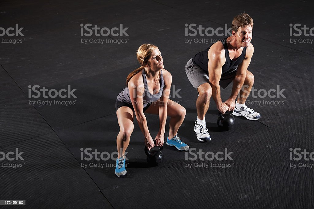Athletes working out with kettle bells stock photo