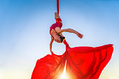 athletic, acrobat gymnast performing aerial exercise with red fabrics outdoors on sky background. flexible woman in red suit performs circus artist dancing in air on silk upside down. sunlight
