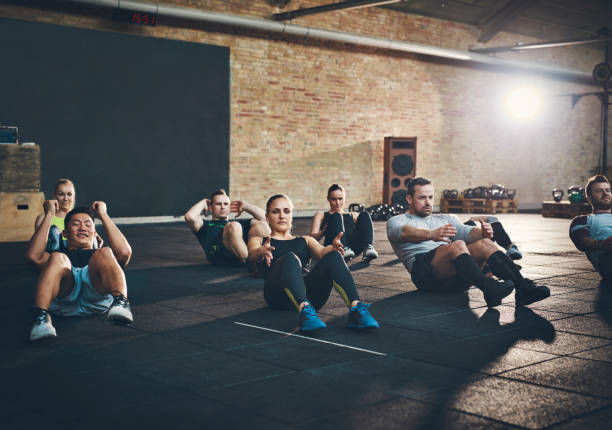 athletic adults performing sit up exercises - sit ups stock photos and pictures