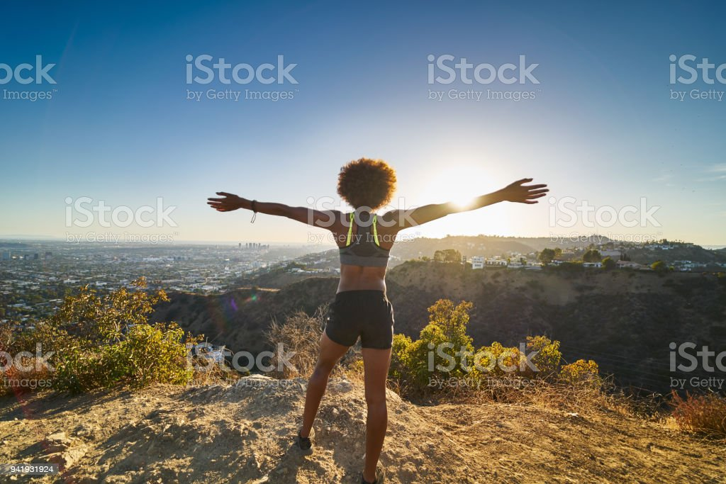 athletic african american woman celebrating reaching top of runyon canyon with arms open royalty-free stock photo