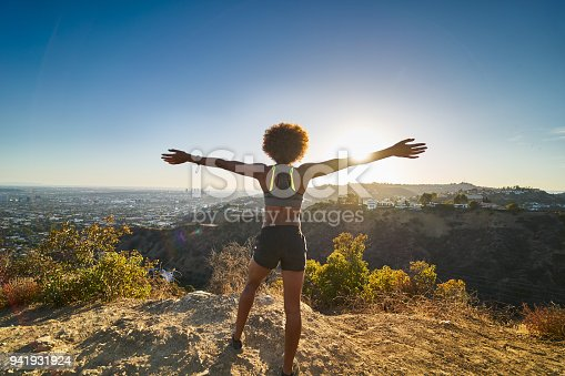 athletic african american woman celebrating reaching top of runyon canyon with arms open shot with lens flare