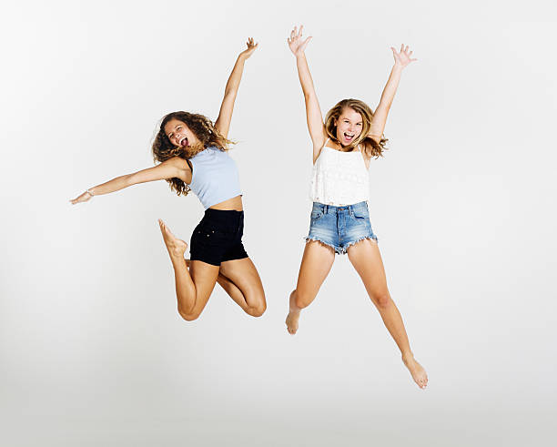 athletic and energetic young beauties jump into the air, laughing - tanz shorts stock-fotos und bilder