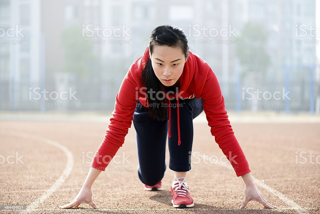 Athletic Asian woman in start position on track stock photo