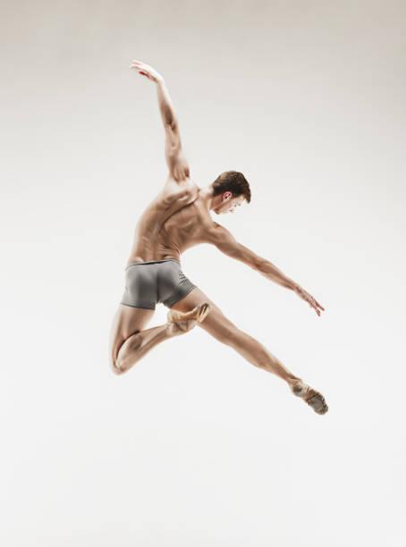 athletische balletttänzer in eine perfekte form über dem grauen hintergrund durchführen - männliche körperkunst stock-fotos und bilder