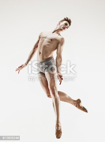 istock Athletic ballet dancer in a perfect shape performing over the grey background 912925246