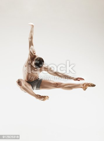 istock Athletic ballet dancer in a perfect shape performing over the grey background 912925318