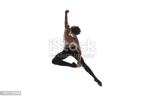 Athletic ballet dancer in a perfect shape performing over the white background.