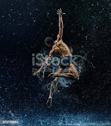 istock Athletic ballet dancer performing with water 970758664