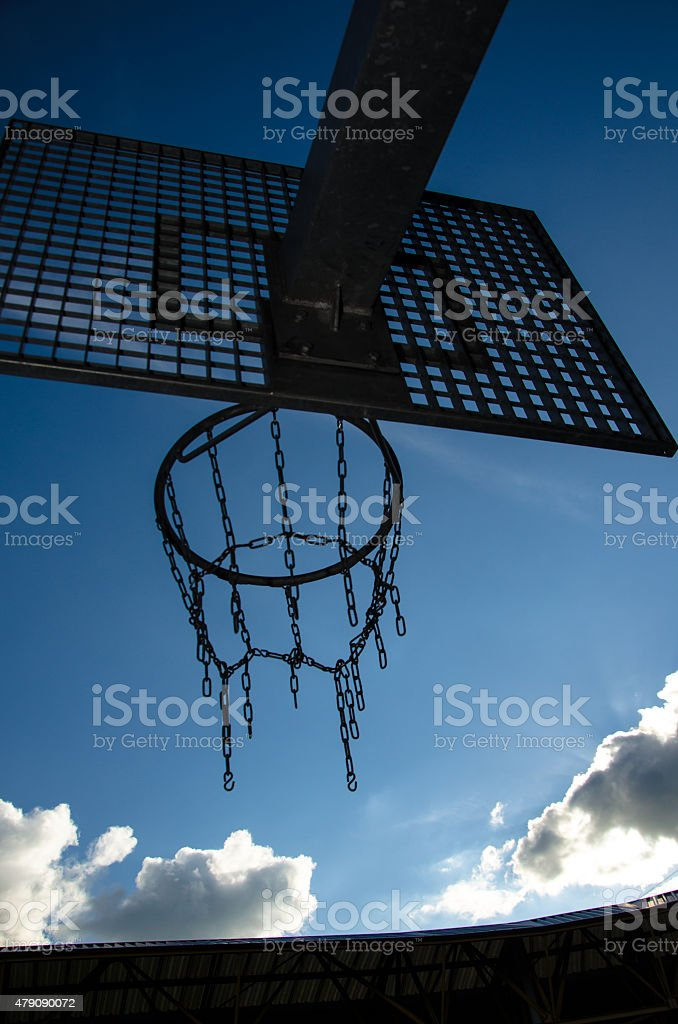 Athletic basketball hoop in stadium looking to blue sky stock photo