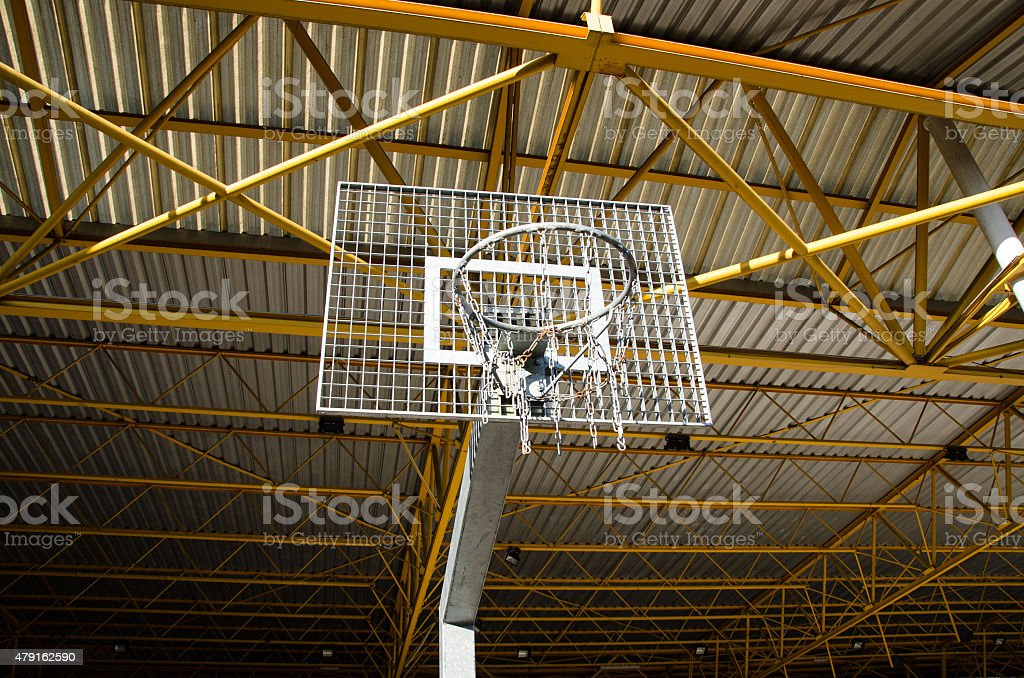 Athletic basketball hoop with steel roof of stadium in background stock photo