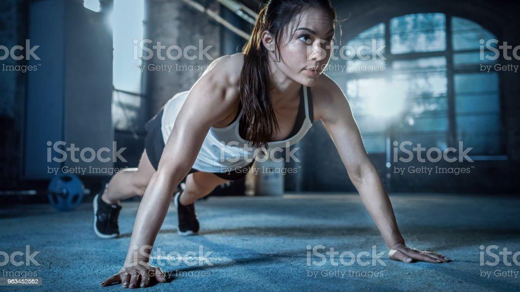 Sportlich schöne Frau macht Liegestütze als Teil von ihr, Bodybuilding-Fitness-Studio-Training-Routine. - Lizenzfrei Anstrengung Stock-Foto
