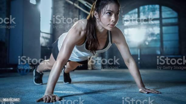 Sportlich Schöne Frau Macht Liegestütze Als Teil Von Ihr Bodybuildingfitnessstudiotrainingroutine Stockfoto und mehr Bilder von Anstrengung