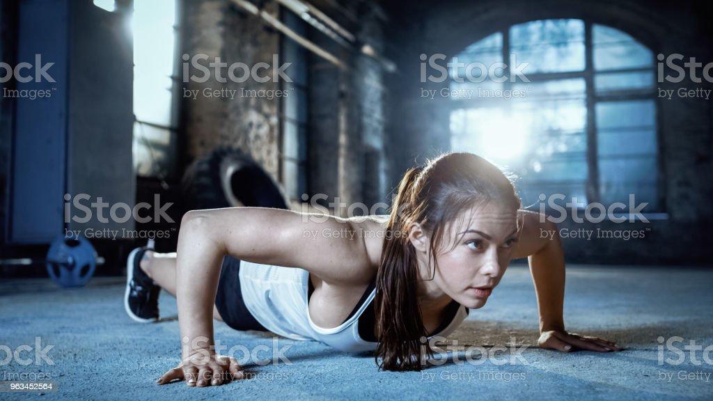 Athletic Beautiful Woman Does Push-ups as Part of Her , Bodybuilding Gym Training Routine. - Zbiór zdjęć royalty-free (Brązowe włosy)