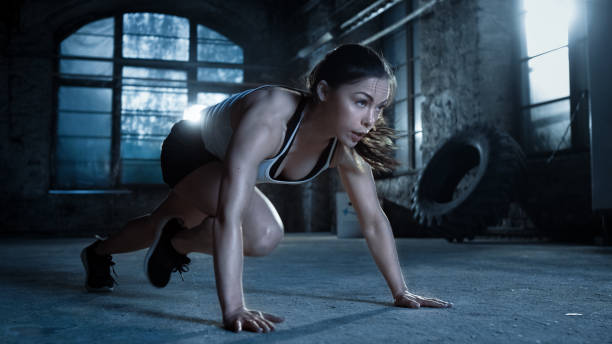 Athletic Beautiful Woman Does Push-ups as Part of Her Cross Fitness, Bodybuilding Gym Training Routine. stock photo