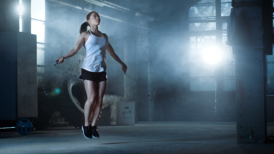 istock Athletic Beautiful Woman Exercises with Jump / Skipping Rope in a Gym. She's Covered in Sweat from Her Intense Cross Fitness Training. Dark atmosphere. 844485748