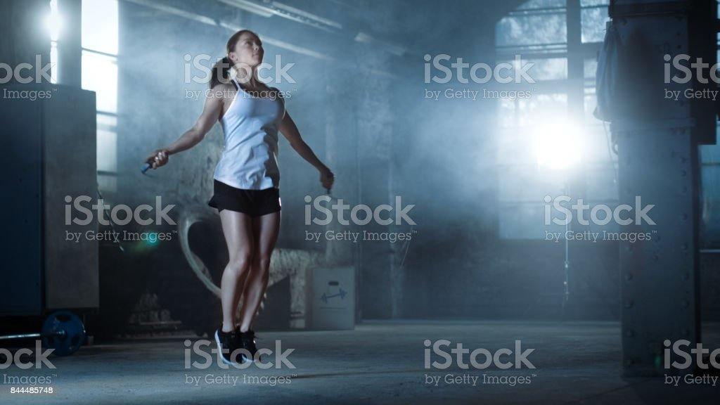 Athletic Beautiful Woman Exercises with Jump / Skipping Rope in a Gym. She's Covered in Sweat from Her Intense Cross Fitness Training. Dark atmosphere. stock photo