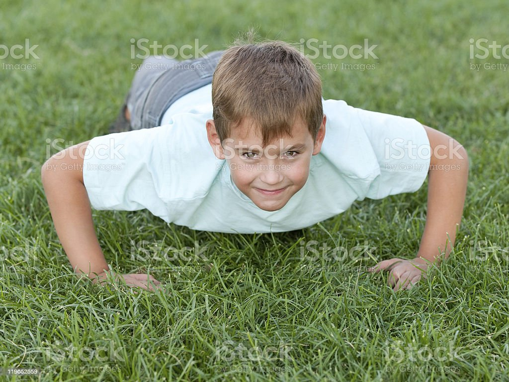 Athletic boy doing push ups on green grass royalty-free stock photo