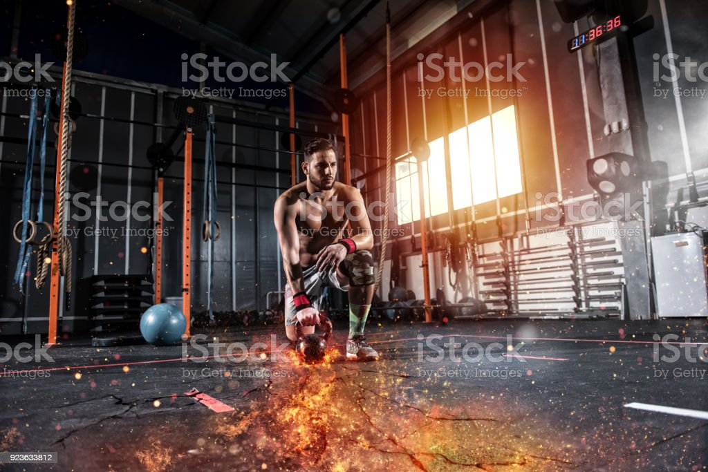 Athletic boy works out at the gym with a fiery kettlebell foto stock royalty-free