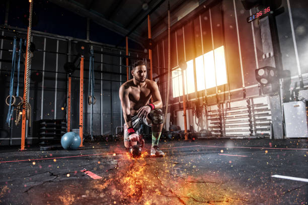 Athletic boy works out at the gym with a fiery kettlebell - foto stock